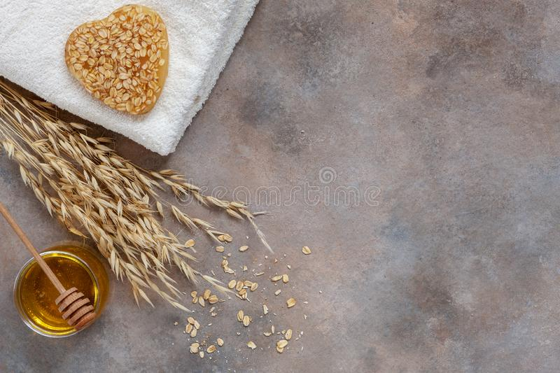 Homemade natural oatmeal soap, fresh honey and towel. Natural skin care. Spa kit for beauty and health. Close up, top view.  stock image