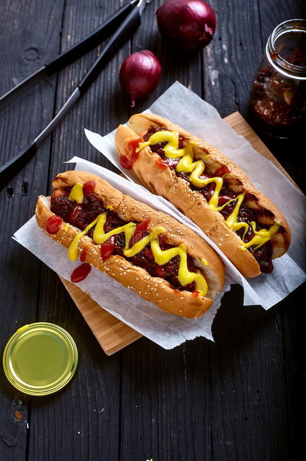 Homemade New York Style Hot Dog with Onion sauce. Dark wood background with onion and tongs on back stock photo