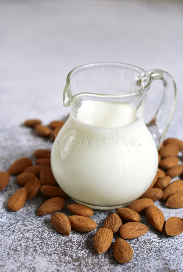 Homemade non dairy almond milk. In a glass pitcher on a white slate, stone or concrete background royalty free stock photo