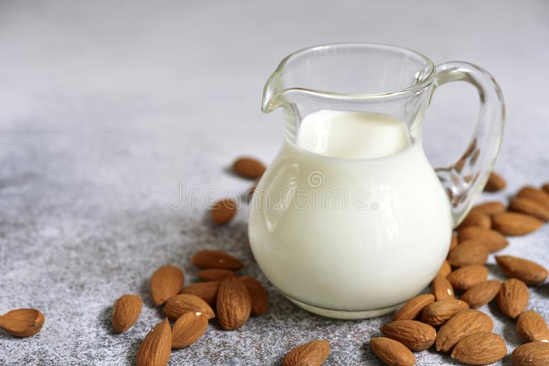 Homemade non dairy almond milk. In a glass pitcher on a white slate, stone or concrete background royalty free stock image