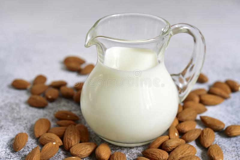 Homemade non dairy almond milk. In a glass pitcher on a white slate, stone or concrete background stock photo