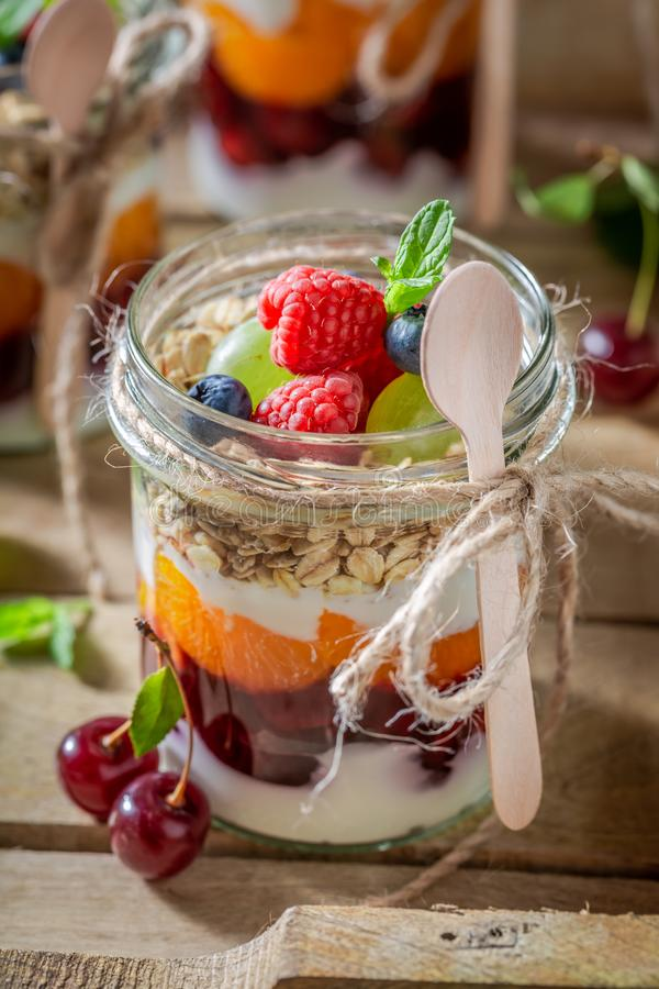 Homemade oat flakes with fresh berries and yoghurt in jar stock photography