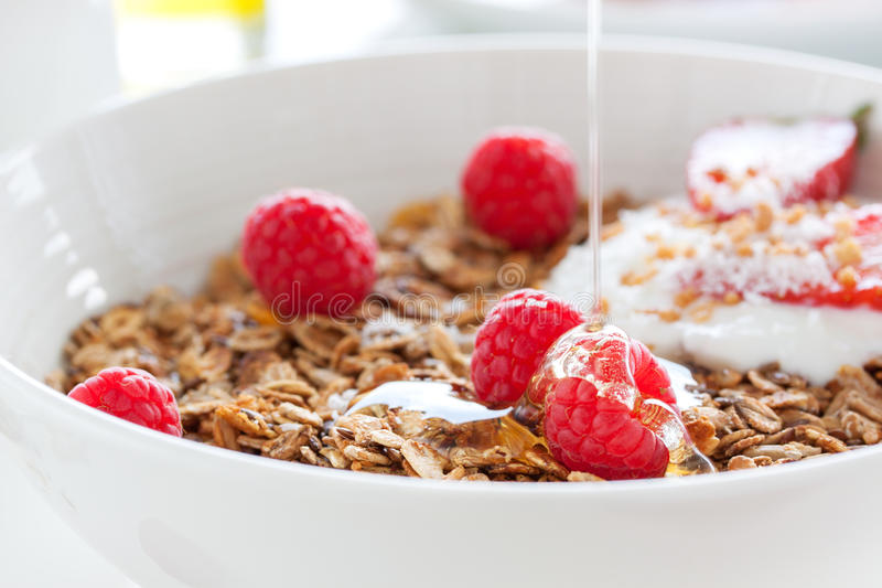Homemade oat meal granola or muesli with fresh summer fruits – raspberry and strawberry with yogurt and honey in a white bowl. On a table for breakfast royalty free stock photo