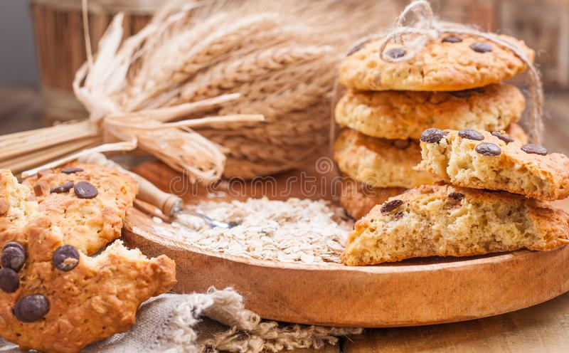 Homemade oatmeal cake for breakfast. Cookies with chocolate on a wooden plate and a bouquet of wheat ears. Free space for text. royalty free stock photo