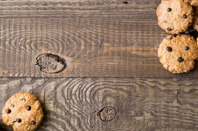 Homemade oatmeal cookies with chocolate drops placed on the old brown wooden table. Place for text stock image