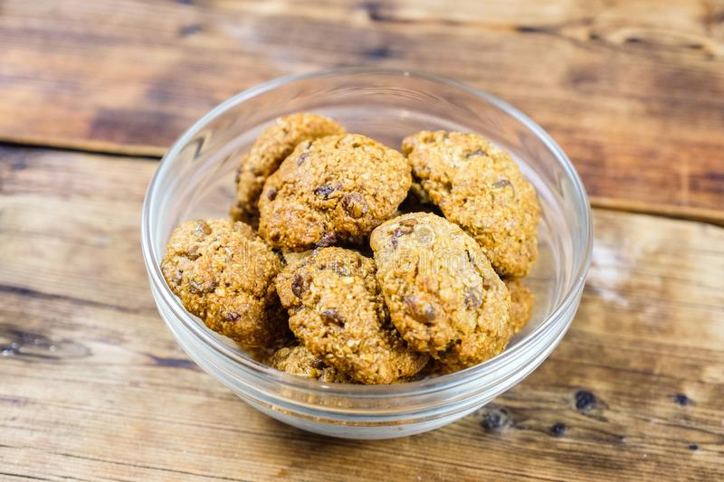 Homemade oatmeal cookies with raisins in glass plate on wooden background. Top view. stock photos