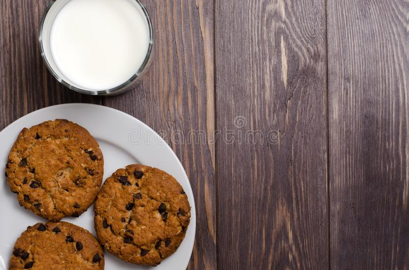 Homemade oatmeal cookies on a white plate and milk. Wooden backg stock photography