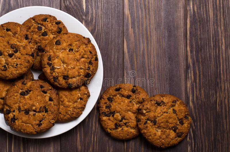 Homemade oatmeal cookies on a white plate. Wooden background. Sp stock photos