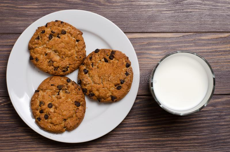 Homemade oatmeal cookies on a white plateand milk. Wooden backgr stock image