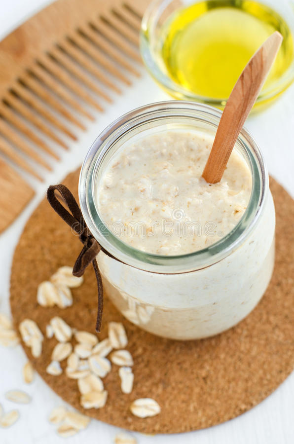 Homemade oatmeal mask in a small glass jar and wooden hair comb. Gentle scrub for sensitive skin royalty free stock photography
