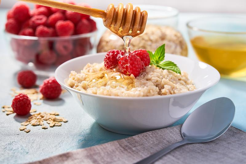 Homemade oatmeal with raspberries for breakfast on a turquoise background. Homemade oatmeal with fresh raspberries for breakfast on a turquoise background royalty free stock photo