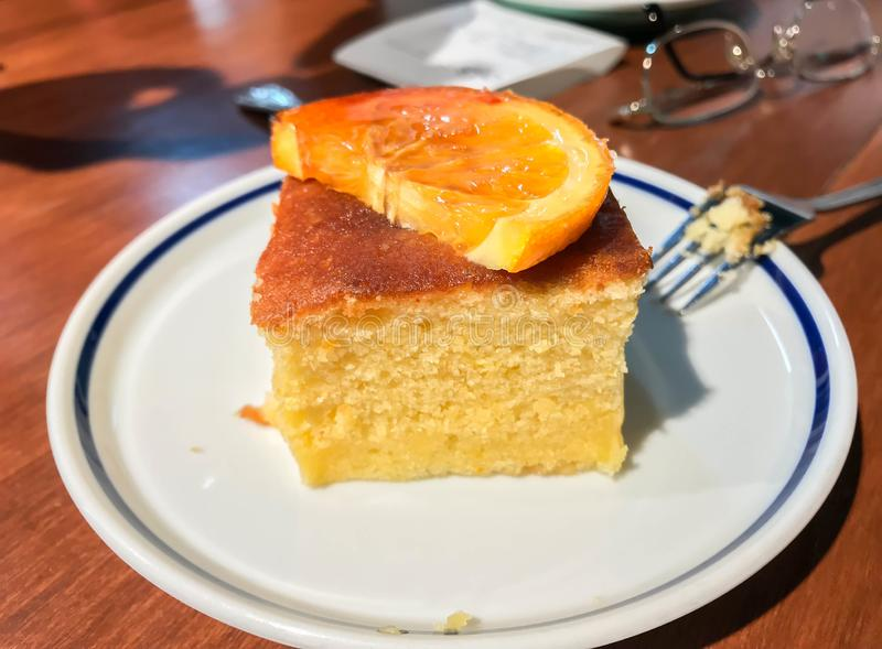 Homemade orange cake with orange slice on white plate with fork stock image
