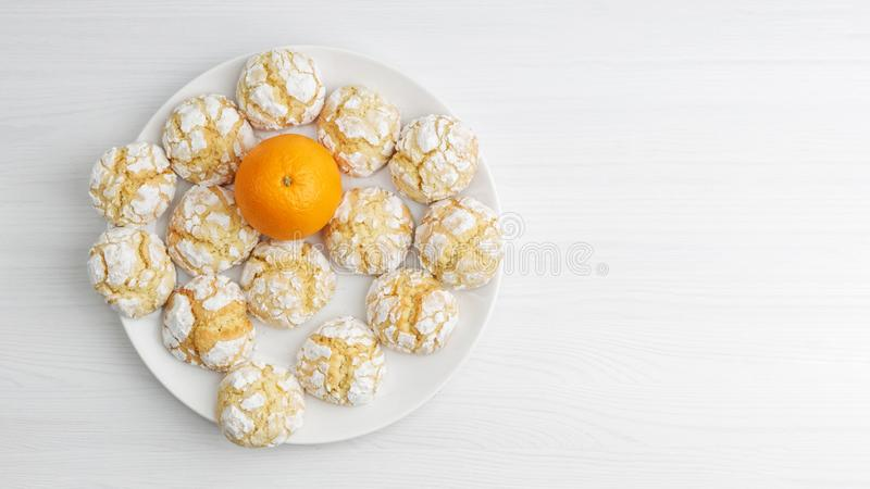 Homemade orange crinkle cookie powdered sugar and orange fruit on white wooden table. Top-down view. royalty free stock photography