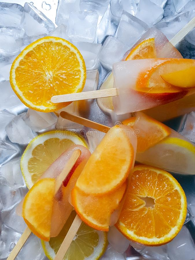 Homemade orange and peach popsicles with ice and citrus slices on light background royalty free stock photo