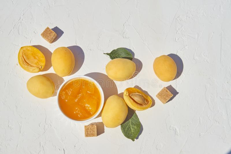 Homemade organic apricot jam and ripe apricots and brown sugar on white background.  stock images