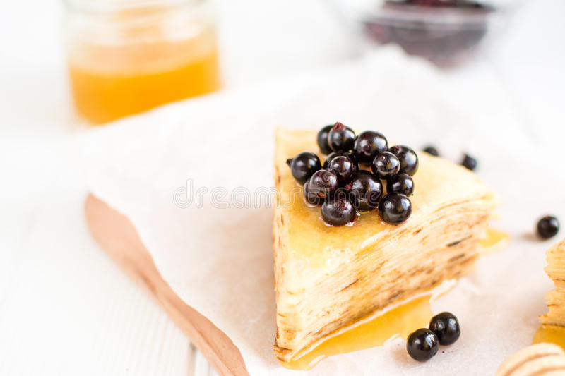 Homemade pancakes with berries and honey on a white background. Delicious homemade pancakes with berries and honey on a white background royalty free stock image