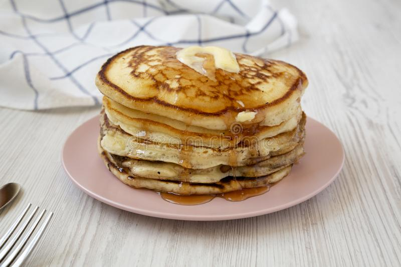 Homemade pancakes with butter and maple syrup on a pink plate, low angle view. Closeup.  royalty free stock photos