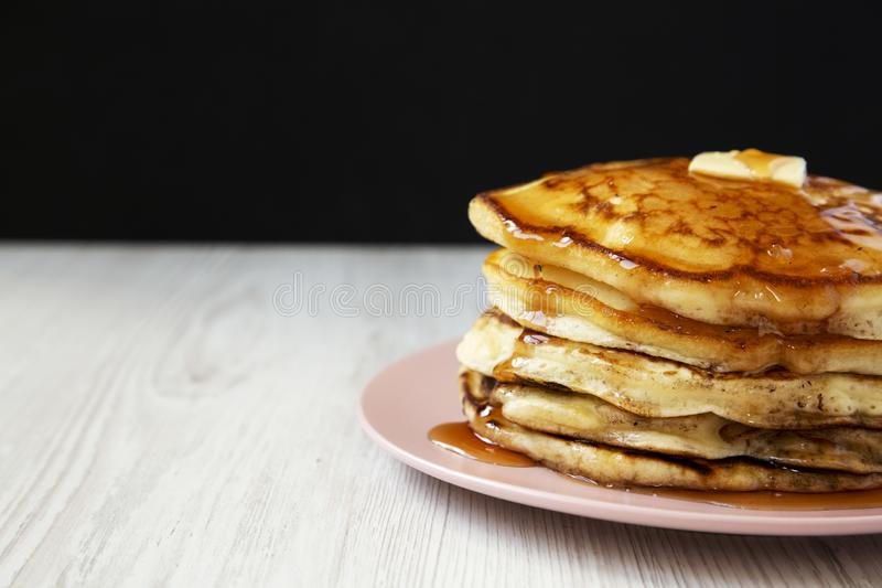 Homemade pancakes with butter and maple syrup on a pink plate, side view. Close-up. Copy space stock photography