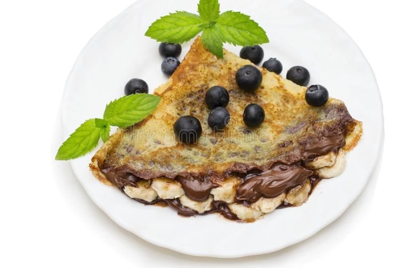Homemade crepes with chocolate cream, banana and blueberries on white background. pancakes. Homemade pancakes with chocolate cream, banana and blueberries on stock image