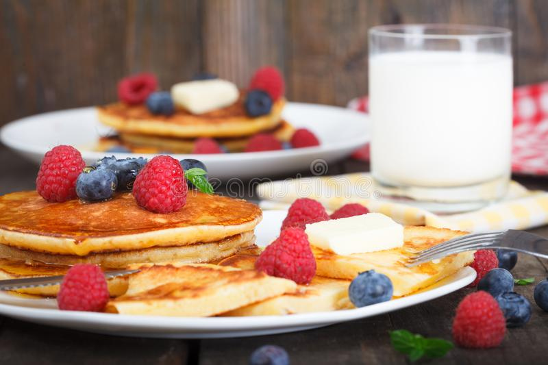 Homemade pancakes with fresh berries, honey and glass of milk stock images
