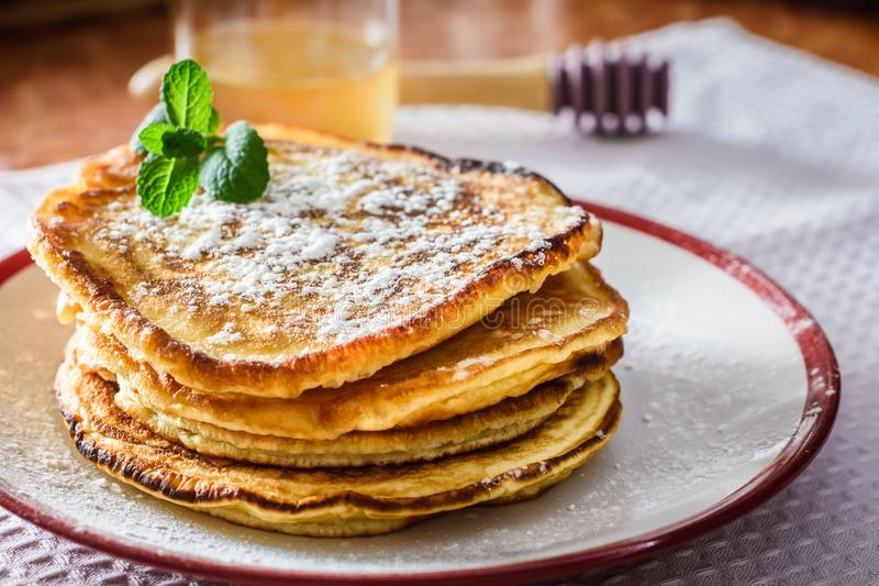 Homemade pancakes with honey. Sweet homemade pancakes with honey and mint on the table stock images