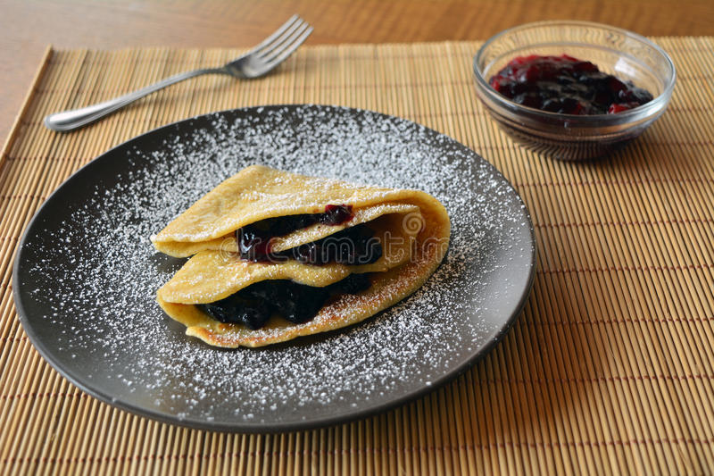 Homemade pancakes with jam and icing sugar. Sweet crepes with strawberry jam and on the plate. Pancakes stock image