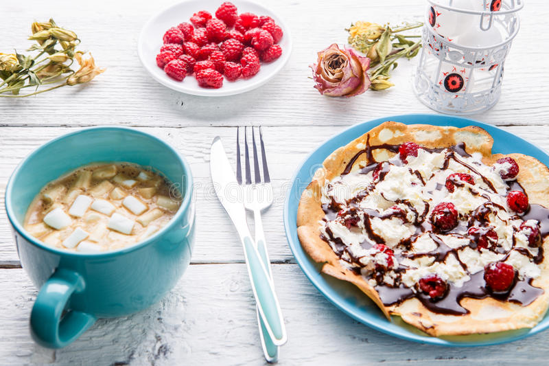 Homemade pancakes or Russian pancakes with chocolate sauce, whipped cream and raspberries on a plate on a white wooden royalty free stock photo