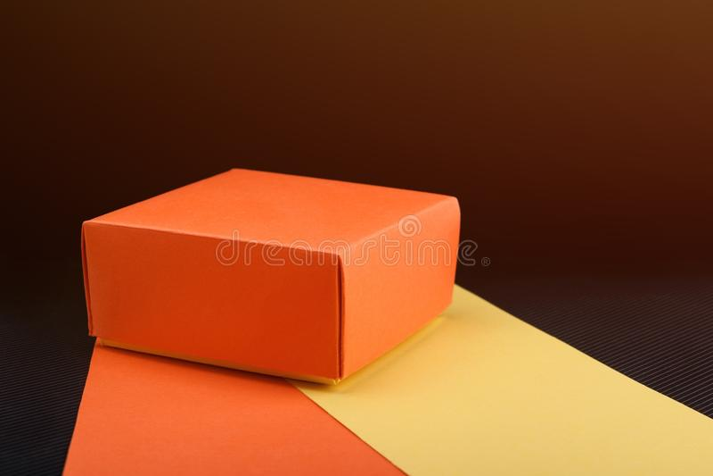 Homemade paper gift box on dark background. Toned light. Homemade orange paper gift box on dark background. Toned light royalty free stock photo