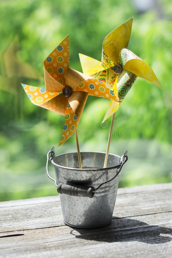 Homemade paper pinwheel in vintage bucket. On a light wooden background stock image