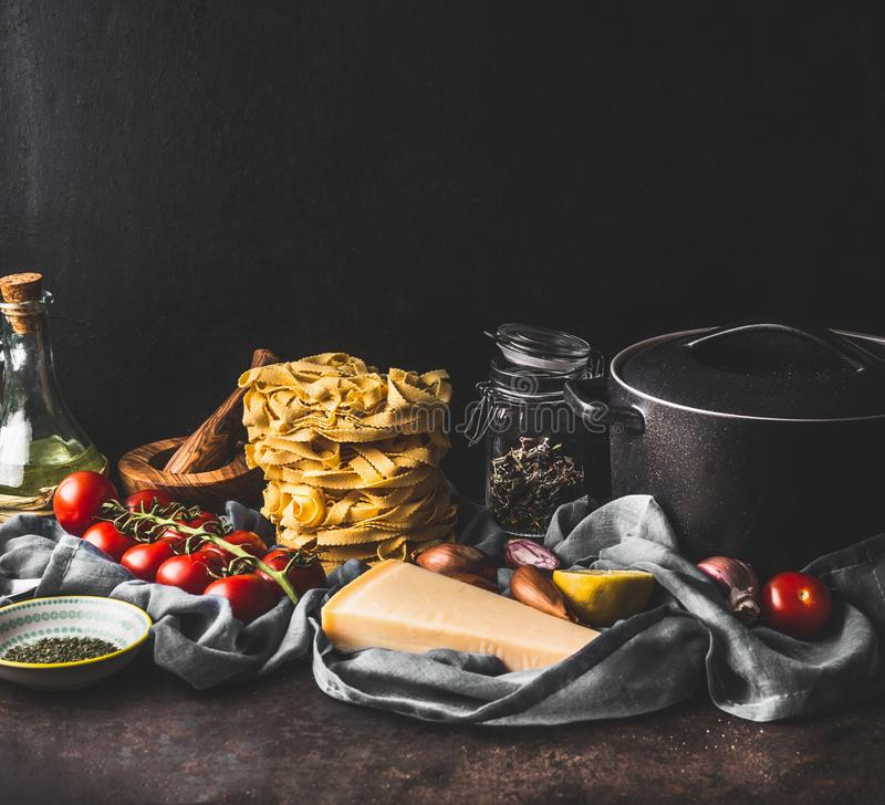 Homemade pasta on dark rustic kitchen counter with pot and fresh ingredients for tasty cooking: tomatoes, olives oil, parmesan, stock photos