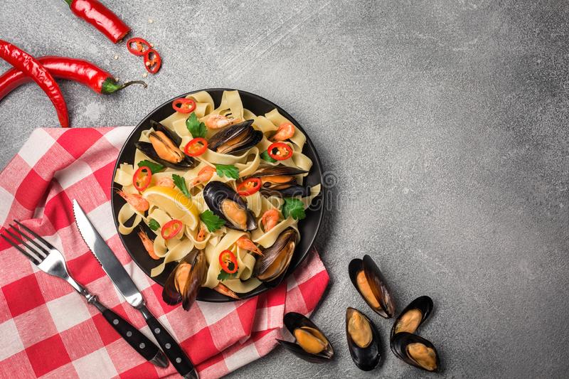 Homemade Pasta Spaghetti with mussels, chilli and parsley on stone background. sea food meal royalty free stock photos