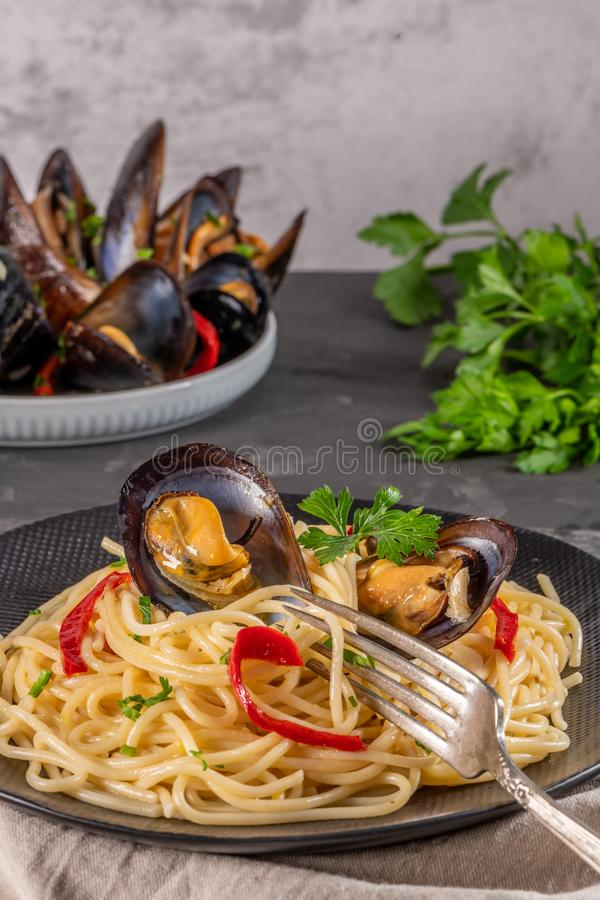 Homemade pasta spaghetti with mussels, peppers and parsley on rustic background. Sea food meal royalty free stock photography