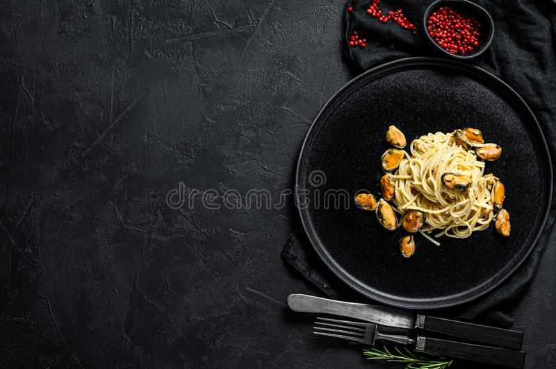 Homemade Pasta Spaghetti with mussels, tomato sauce on black background. sea food meal. space for text royalty free stock image