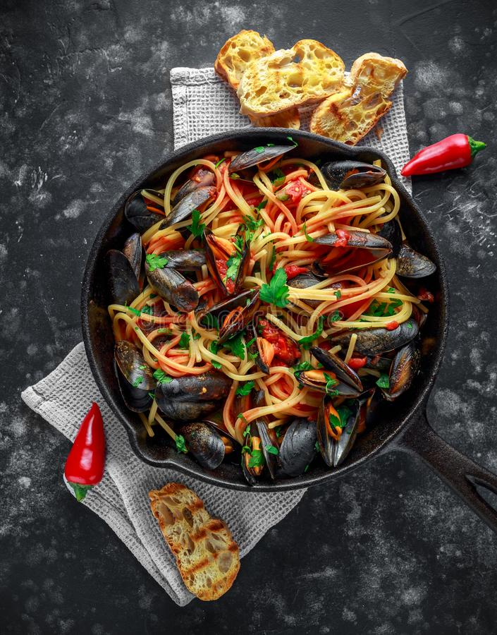 Homemade Pasta Spaghetti with mussels, tomato sauce, chilli and parsley in rustic skillet, pan. sea food meal stock image