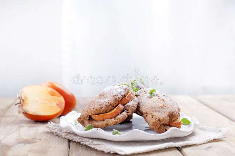 Homemade pastries with fresh persimmons, for breakfast, white plate on a napkin. Wooden table. Free space for text or advertising royalty free stock photos