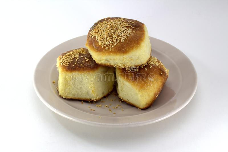 Homemade pastries, ruddy buns with sesame seeds on a pearl plate on a white background stock photos