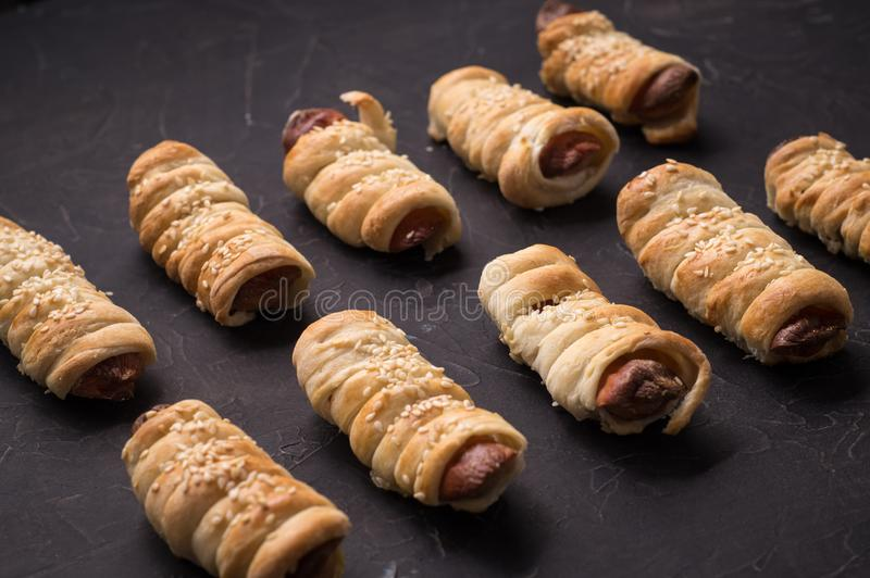 homemade pastries: several sausages in a dough on a black background. stock photos