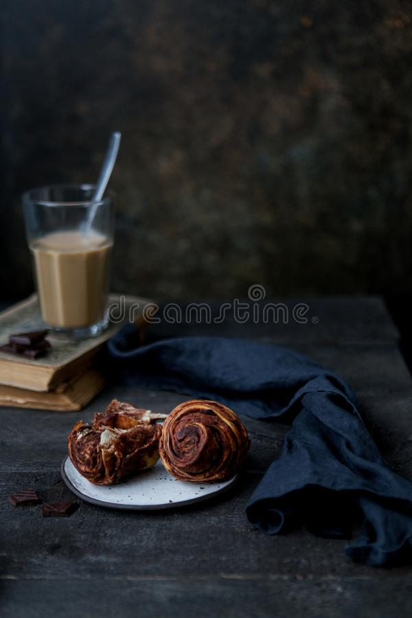 Homemade pastry cinnamon rolls with custard and raisins over old dark blue wooden background. Top view, space. Rustic style royalty free stock images