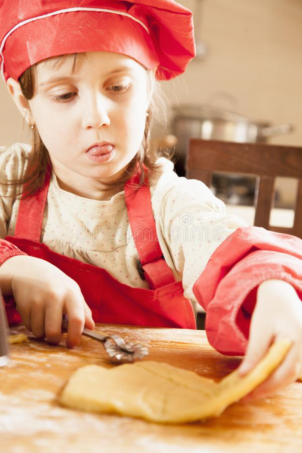 Homemade pastry. Cute little child girl chef cooking cakes dough on wooden desk with flour royalty free stock image