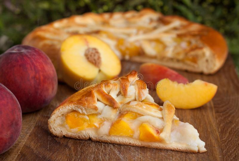 Homemade peach pie on wooden desk, close up royalty free stock image