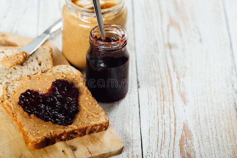 Homemade peanut butter and jelly sandwich on wooden background. Homemade peanut butter and heart shaped jelly sandwich on wooden background royalty free stock photos
