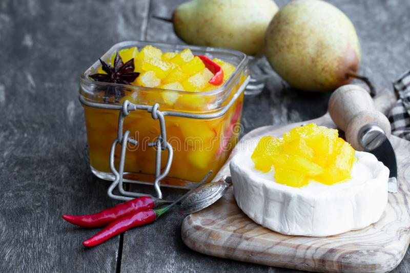 Homemade pear and chilli pepper chutney with goat cheese on wooden table royalty free stock image