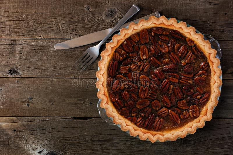 Homemade pecan pie, top view over wood. Homemade pecan pie, top view with a dark rustic wood background stock photography