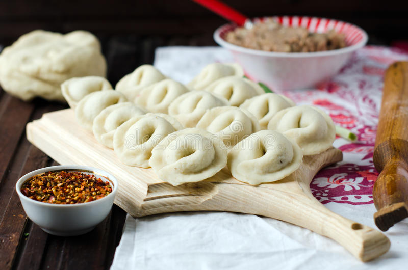 Homemade pelmeni. Dumplings, home-made on a wooden Board royalty free stock images