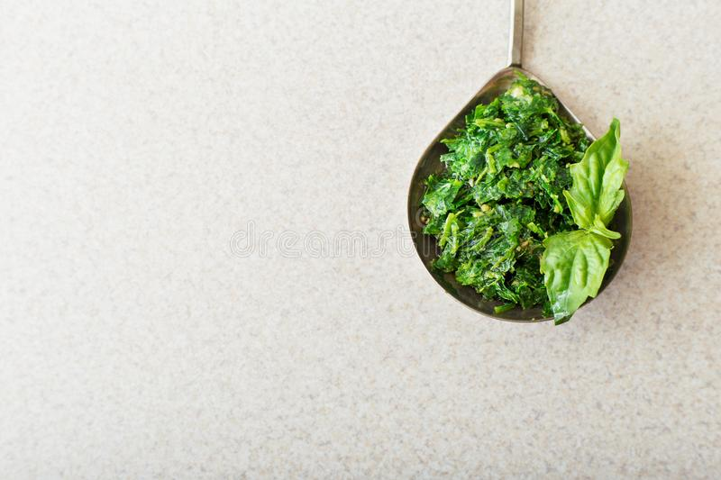 Homemade pesto sauce in a spoon with basil on white table in the kitchen. Top view with copy space. Pesto - traditional italian royalty free stock photography