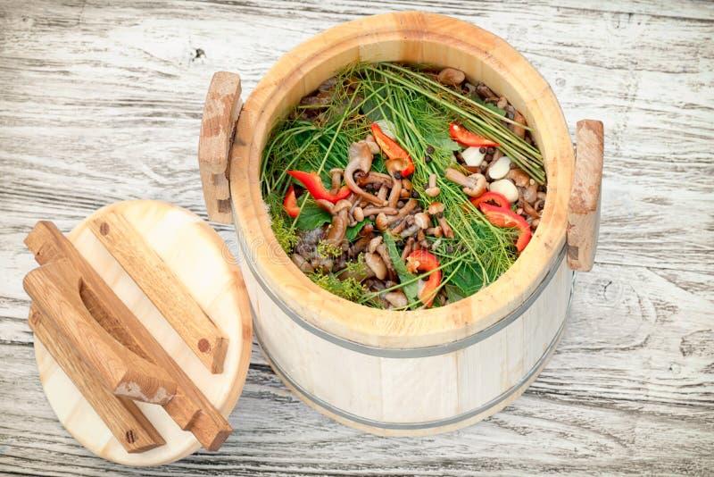 Homemade pickled honey agaric mushrooms in wooden keg royalty free stock photo