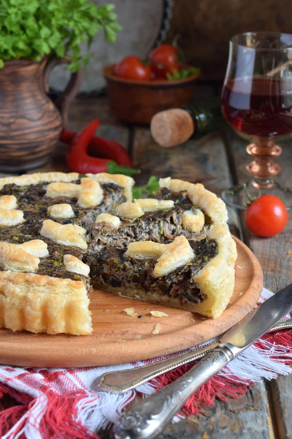 Homemade pie with mushrooms and herbs. Quiche on wooden background. Vegetarian food. stock images