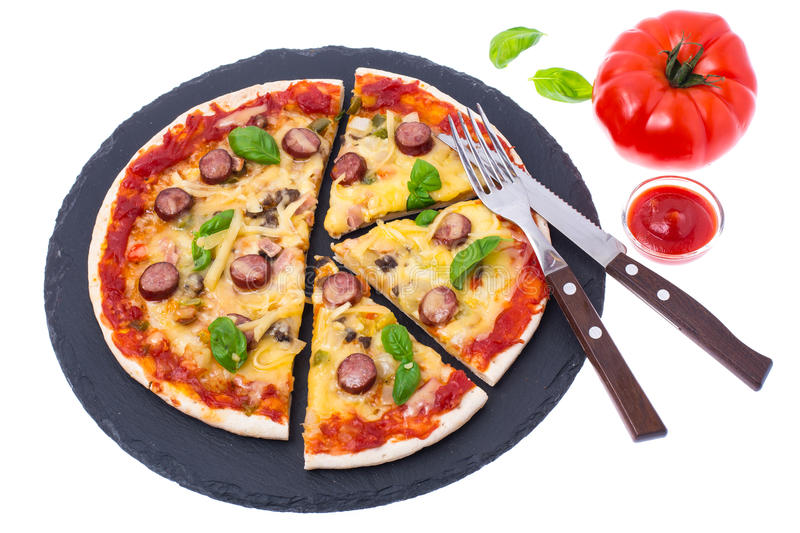 Homemade pizza on black stone plate stock photo