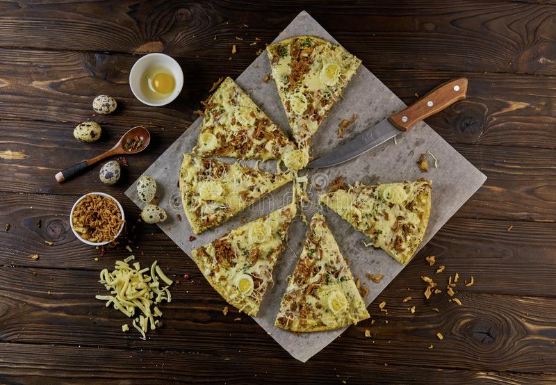 Homemade pizza cut in slices on baking paper over wooden background, top view,. Homemade pizza cut in slices on baking paper on wooden table royalty free stock image