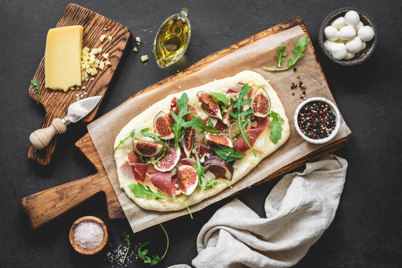 Homemade pizza or flatbread with figs, ham, arugula, cheese royalty free stock photo